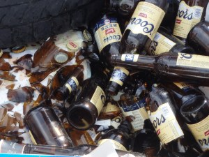 Beer bottles discarded in a dumpster... by the recycling bin.